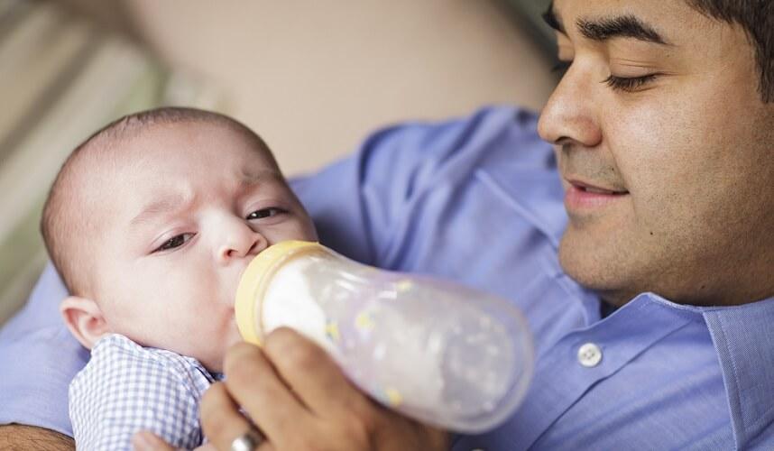 man bottle feeding baby