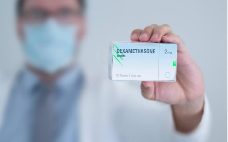 Image of doctor holding box of dexomethasone corticosteroid medicine