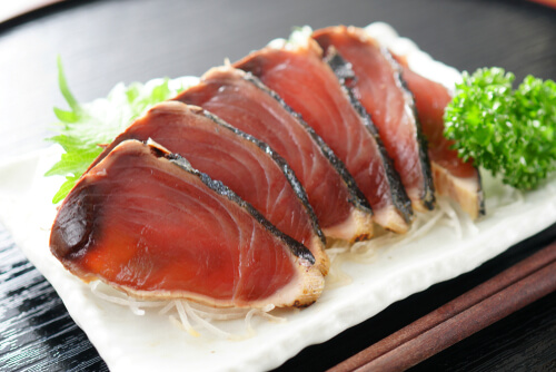 Slices of skipjack tuna sashimi displayed on a white service plate