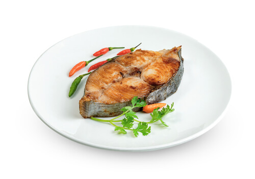 A steak grilled fish presented on a white plate with a garnish of chilis and cilantro.