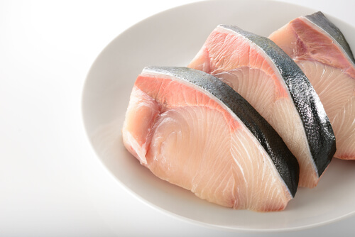 Several yellowtail steaks on a white plate with a white tabletop background